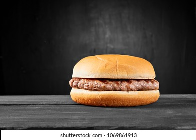 Plain beef burger on wooden table isolated on black background.