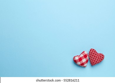 Plain blue background with two little, red heart