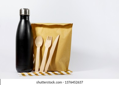 A plain brown paper lunch bag with eco friendly, biodegradable cutlery and straws and a reusable stainless steel water bottle. Plastic single use alternative. Isolated on a white background