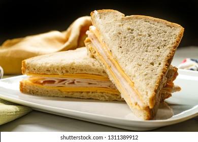 Plain cheese turkey and mayonnaise sandwich on healthy whole wheat oatnut bread cut in triangles