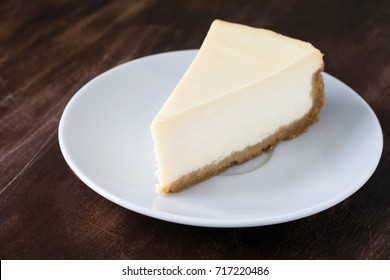 Plain cheesecake slice on white plate on wooden table. Closeup view, selective focus, horizontal
