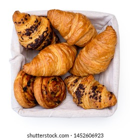 Plain and chocholate croissants and rasin danish pastry swirls in linen basket isolated on white from above.