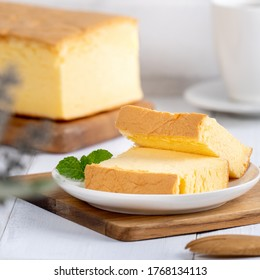 Plain classic Taiwanese traditional sponge cake (Taiwanese castella kasutera) on a wooden tray background table with ingredients, close up.