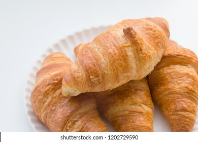 Plain croissants on top of each other on the plate, white table background