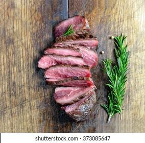 Plain cut juicy beefsteak on a wooden board, top view