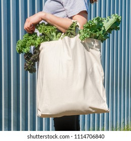 Plain flex eco-bag with green fresh kale and arm on the background of the metal fence or wall
