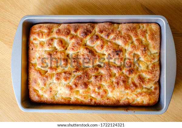 plain focaccia in pan on wood table