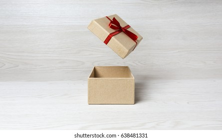 plain gift box, cover on the air with red bow on white wooden background