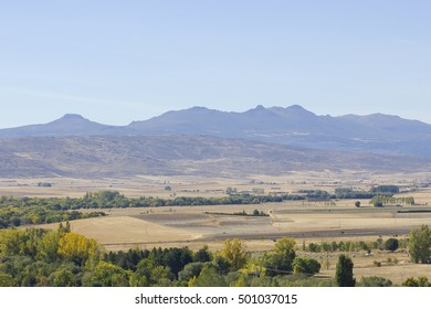Plain terrain with dry land farm surrounded by mountains