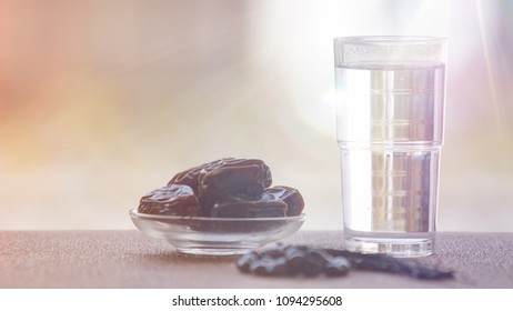Plain water and dates, typical menu during breaking fast in the holy month of Ramadhan for muslim over the world. Added light leaks editing. Soft focus due to shallow depth of field