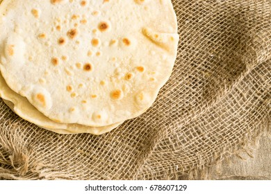 Plain Wheaten Flat Bread on a Burlap Background Top View. Fresh Homemade Flatbread also known as Pita Bread, Chapati, Naan or Tortilla