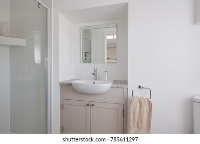 Plain white decorated white shower room closet with shower cubicle, handbasin inset into a built-in cuboard, towel, mirror w.c. and soap dispenser