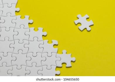 Plain white jigsaw puzzle, on Yellow background.