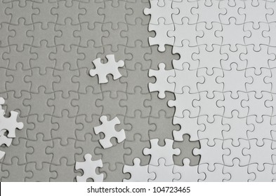 Plain white jigsaw puzzle, on Gray background.