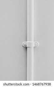 Plain white thin vertical plastic pipe affixed to a blank seamless white wall.