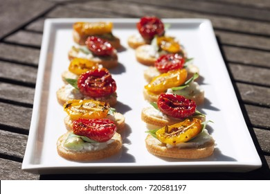 Plain white tray or plate displaying canapés in alfresco setting