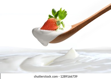 Plain yogurt on a spoon with fresh  strawberry on top hanging above of plain yogurt isolated on white background