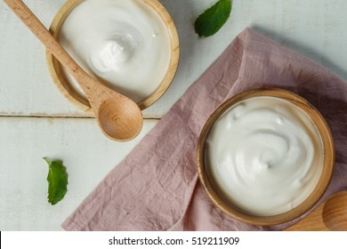 Plain Yogurt in wooden bowl on wooden background with pink cotton and spoon, Health food from yoghurt concept
