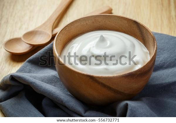 Обычный йогурт в деревянной чаше на деревянном фоне с синим хлопком и ложкой, Здоровое питание из йогурта концепции