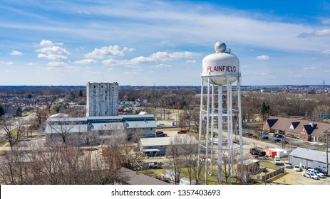 PLAINFIELD, IL, USA - MARCH 19, 2019:  A drone / aerial view of a white water tower with Plainfield painted in red with an old grain elevator standing high in the background.