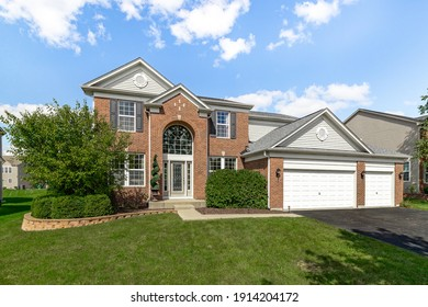 PLAINFIELD, IL, USA - SEPTEMBER 15, 2020: A beautiful, brick two story house with a three car garage, arch doorway, and brick landscaping.