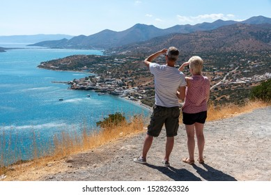 Plaka, eastern Crete, Greece. September 2019.  Holidaymakers overlook the coastal village of Plaka and the Mirabello Sea from a mountain road