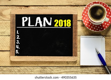 Plan 2018/ Plan 2018 on blackboard with cup of coffee, notebook and pen on wooden background.