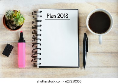 Plan 2018 written in a notebook / Notebook with an Plan 2018 on wooden desk with cup of coffee