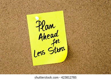 Plan Ahead For Less Stress written on yellow paper note pinned on cork board with white thumbtack, copy space available