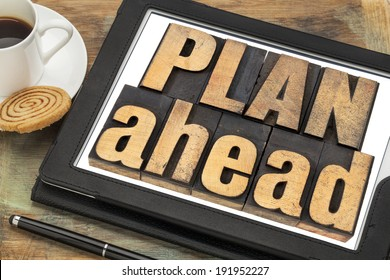 plan ahead phrase in letterpress wood type on a digital tablet with a cup of coffee