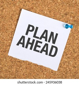 Plan Ahead Reminder Note Pinned to a Cork Memory Bulletin Board in Business Office