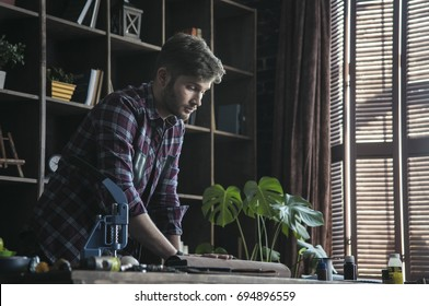 Plan for day. Young man leather maker standing at table and hold roll of brown leather in workshop. Fashion homemade studio. Small business from hobby