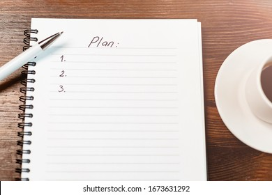 Plan with to do list and coffee with phone on wooden table