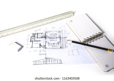 plan and elevation of home preliminary design sketch by black pencil on white paper and white background with drawing tools, scale rulers, small sketch book, selective focus