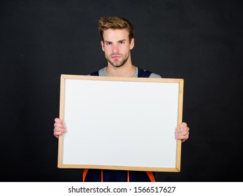 Plan repair work using blueprints or diagrams. Troubleshoot and fix faulty electrical switches. Repairman engineer hold whiteboard copy space. Handsome repairman. Man repairman builder work clothes.
