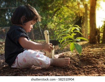 plan saving concept, kid sitting for planting and gardening with sunlight