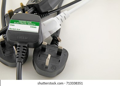 plan view of plugs – Blurred background of  three pin plugs with top of plug  with test sticker
