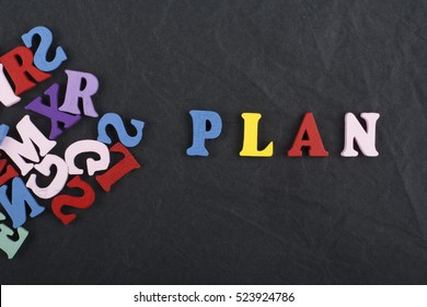 Plan word composed from wooden letters on black board background, study planning concept, start your life plan