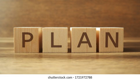 PLAN word made of wooden cubes on a brown background, business concept. Banner.