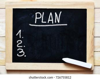 Plan word written on chalkboard on wooden background