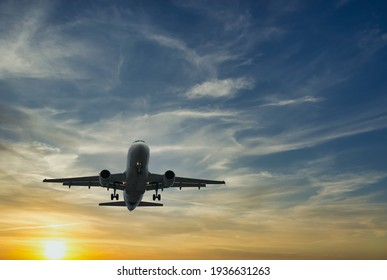 The plane against the blue sunset sky. The setting sun. Sunset. - Shutterstock ID 1936631263