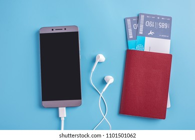 Plane, air tickets, passport, glasses and phone with headphones on a blue background. The view from the top. The concept of planning and preparing for the travel