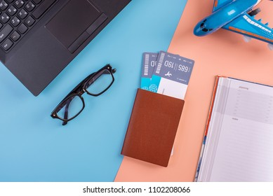 Plane, air tickets, passport, notebook and phone with glasses on pastel background. The view from the top. The concept of planning and preparing for the travel