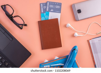 Plane, air tickets, passport, notebook and phone with headphones on a pink background. The view from the top. The concept of planning and preparing for the travel