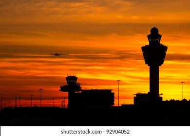 Plane arriving at Amsterdam-Schiphol airport during sunset