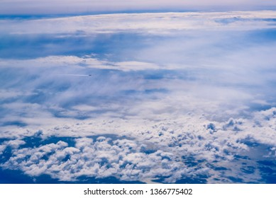 Plane of commercial flights crossing a sky of blue and white clouds seen from above, on the Mediterranean.
