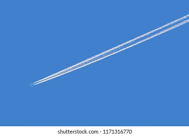 plane with condensation trail in front of blue sky