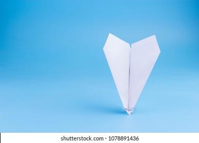 plane crash concept. paper plane upside down on blue background