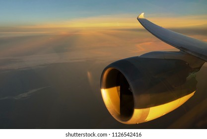 Plane engine and wing against a sunrise backdrop