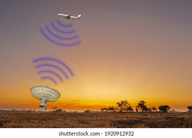 The plane flew in the sky communicating with the satellite station or radar on ground as the sun rises in the morning